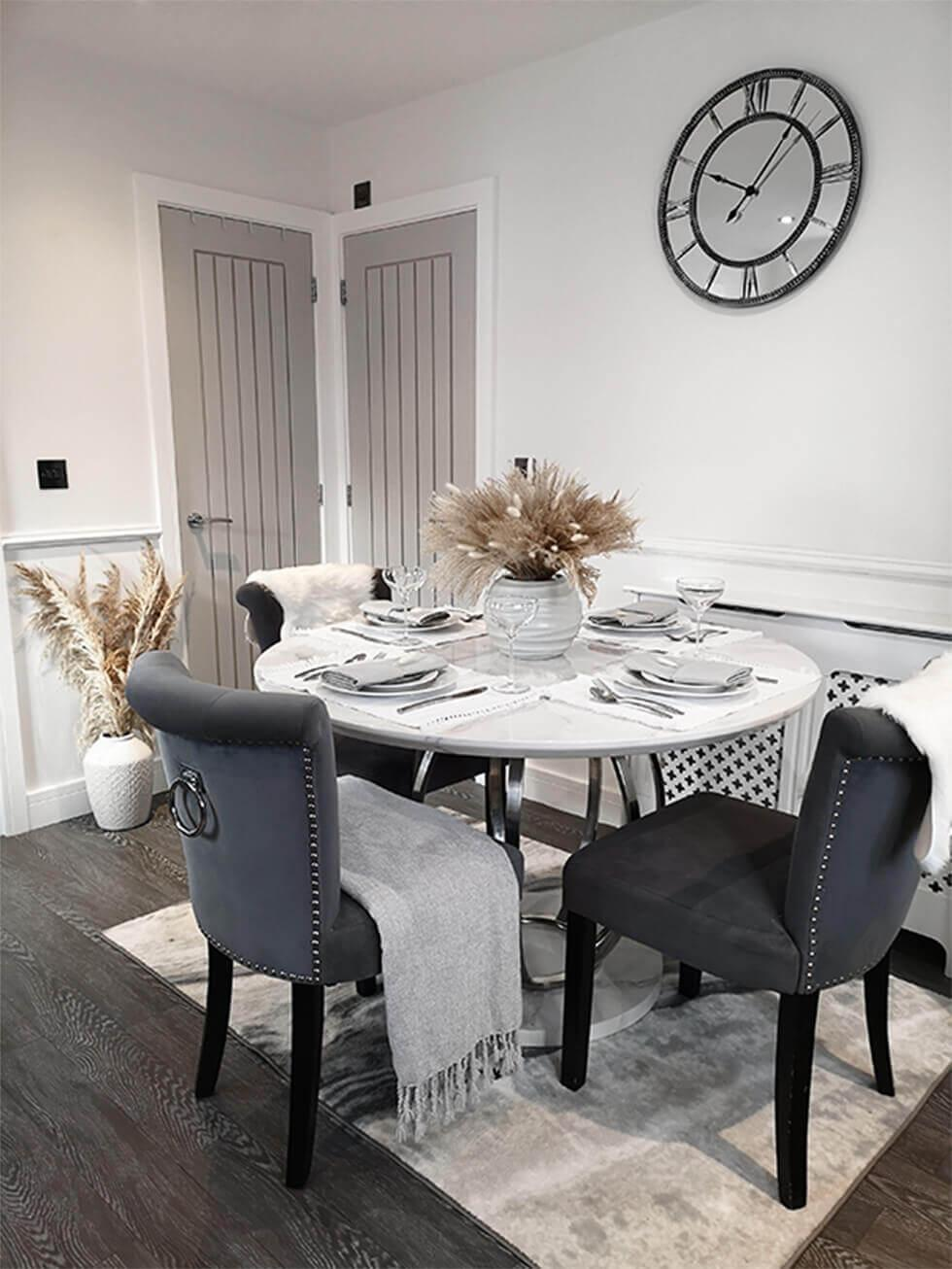 Open plan dining space with round marble table, grey fabric dining chairs and grey doors