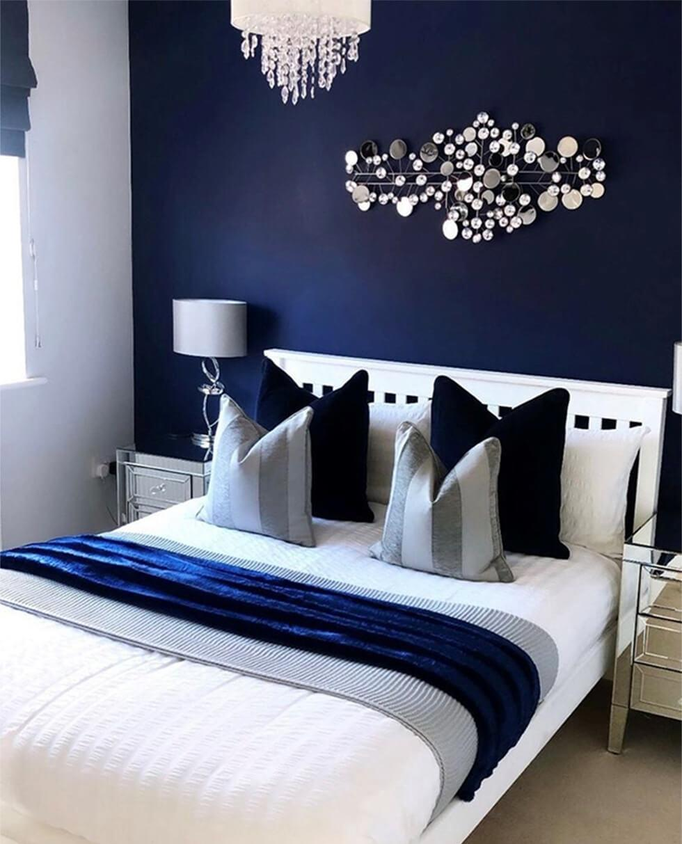 bedroom with dark blue walls and mirrored bedside tables