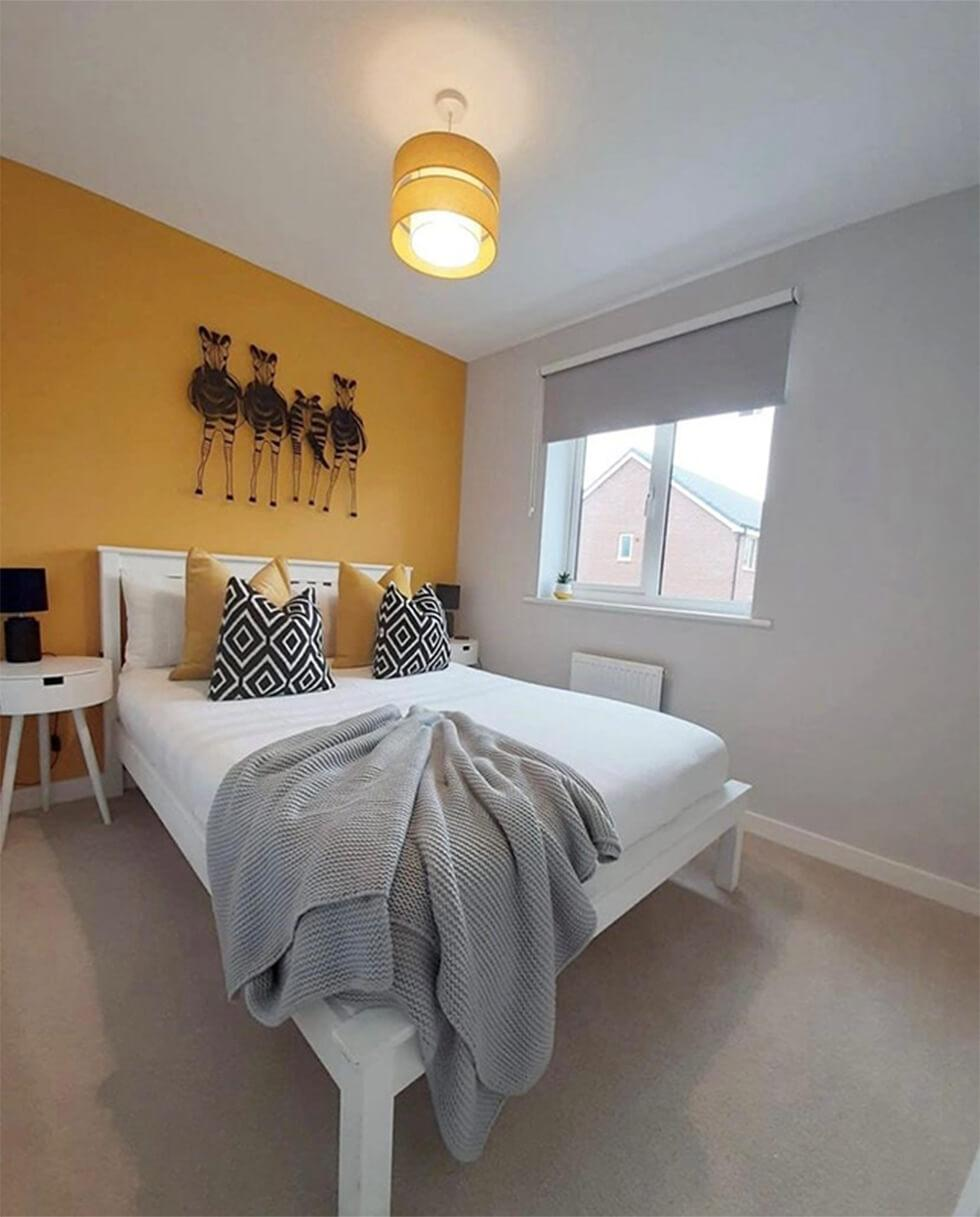 guest room with yellow walls and white bed