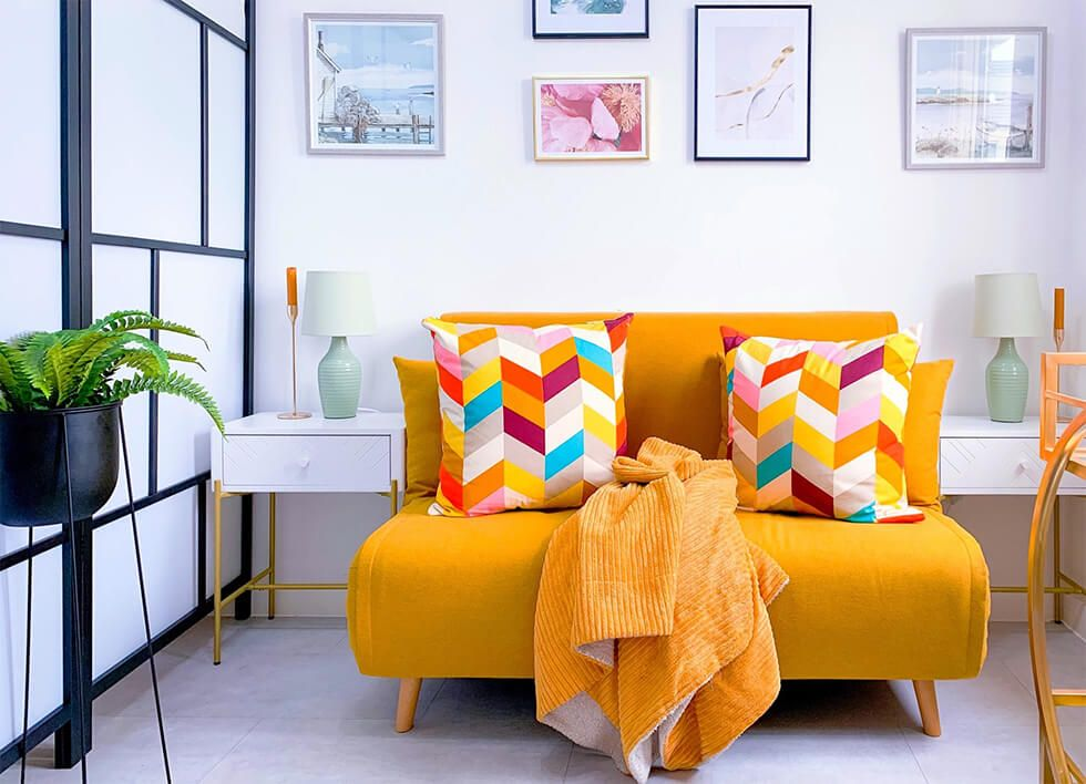 White living room with a mustard sofa decorated with colourful cushions