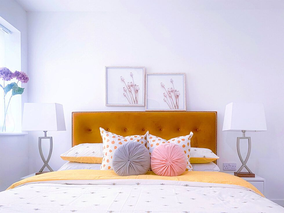 All white bedroom centred with a mustard bed and decorated with colourful pillows