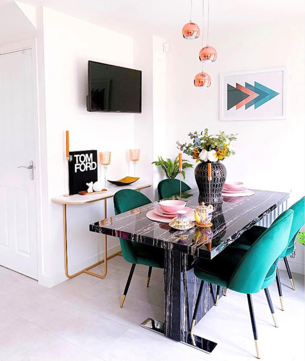 Glam dining space with a black marble table and emerald green chairs
