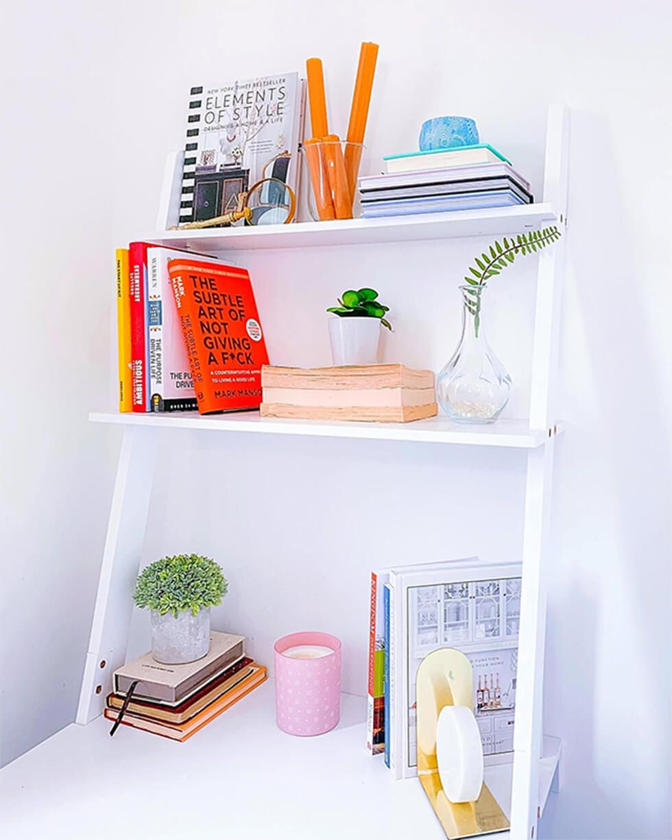 White shelf arranged neatly with colourful books and small plants
