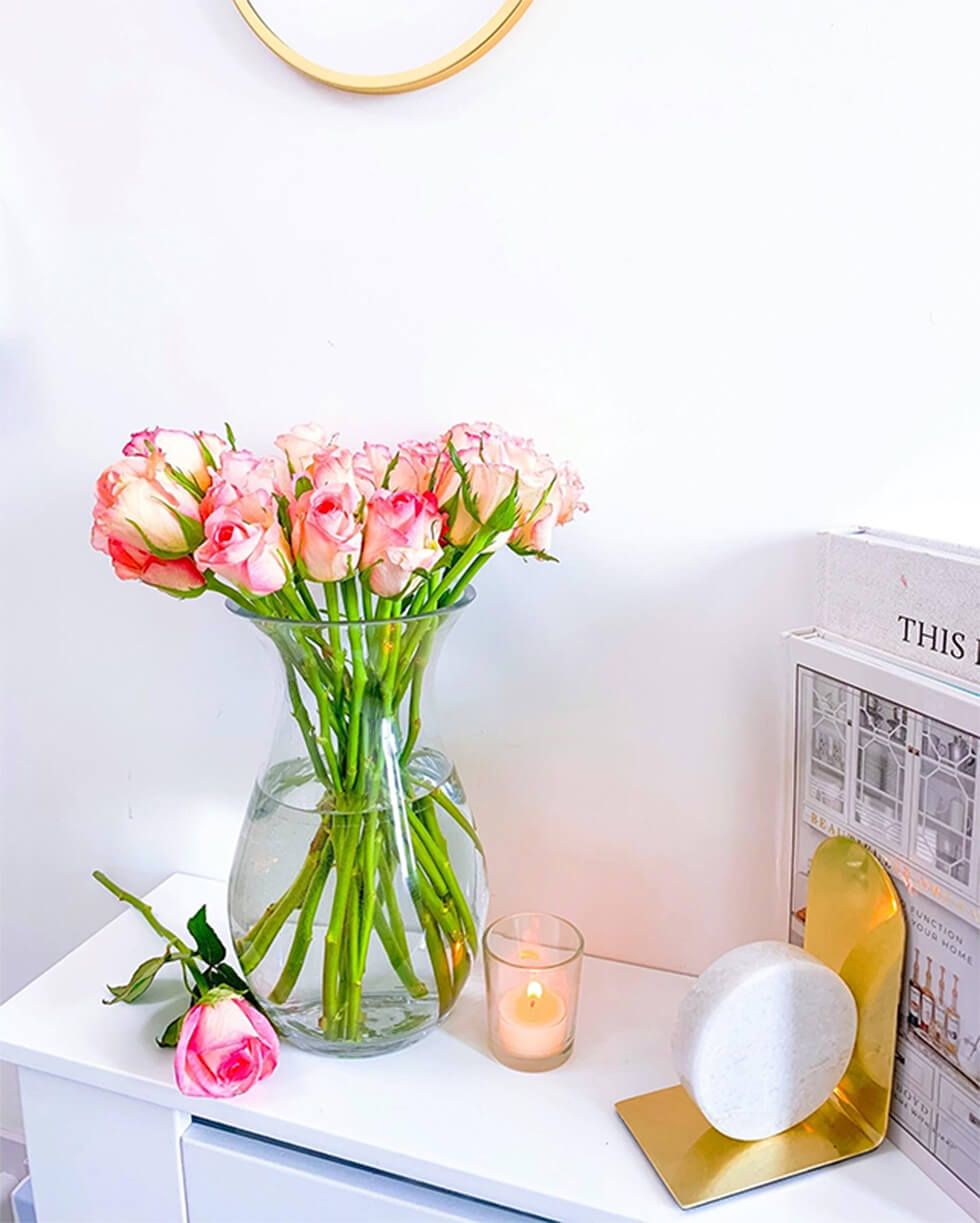 A bouquet of pink roses next to a candle