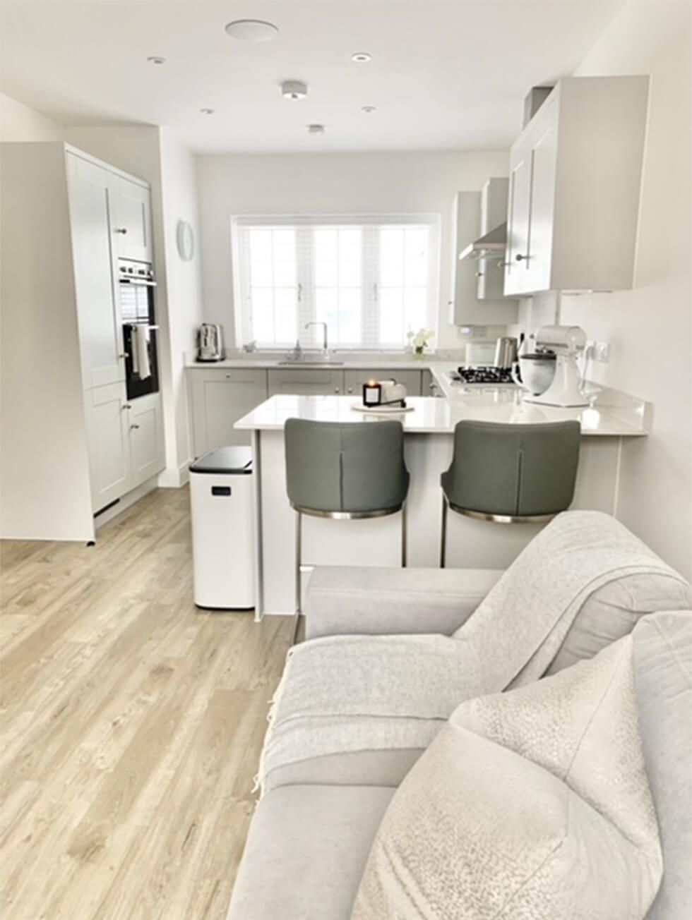Modern all-white kitchen with a breakfast island, bar stools and sofa next to it