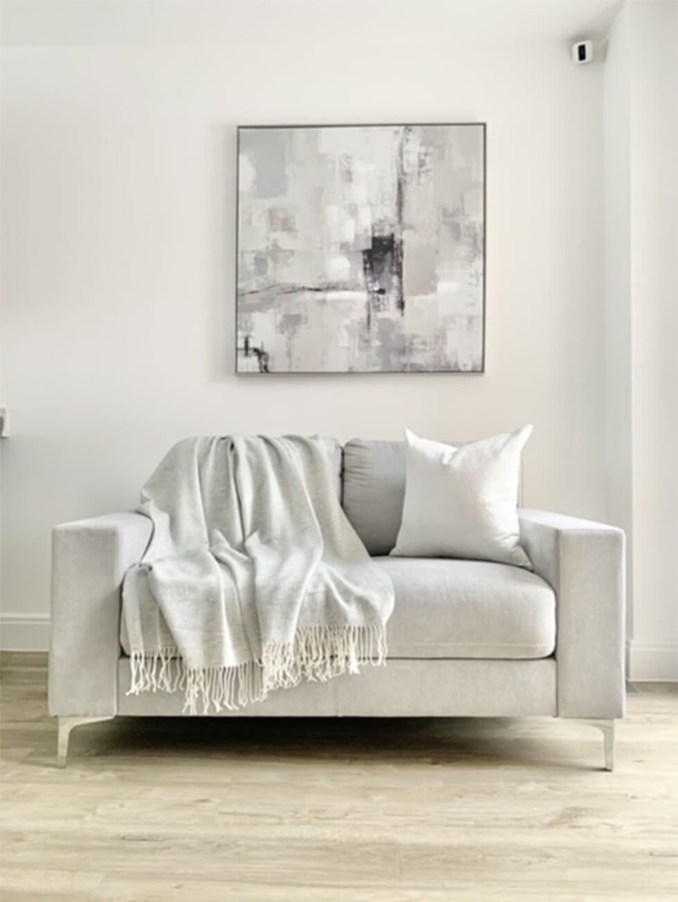 Modern light grey Baltimore sofa and abstract wall art above it