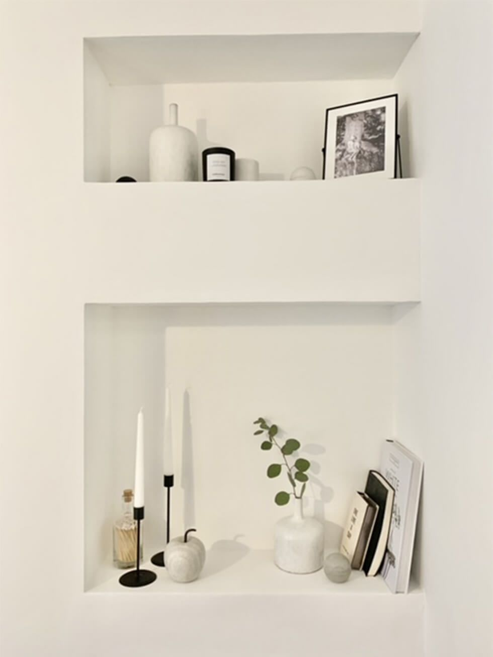 Minimalist wall niche decorated with candles, vases and books