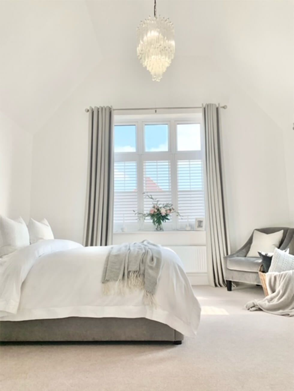 Elegant neutral bedroom decorated with an armchair, double bed and chandelier
