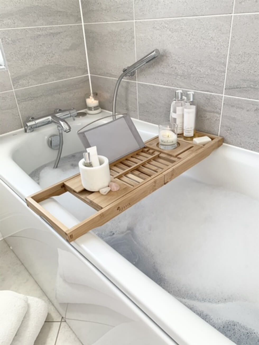 A bubble bath with a wooden bath tray decked with toiletries and a scented candle