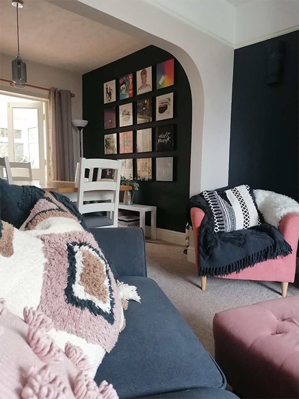 Grey sofa with textured cushions in a black and pink living room