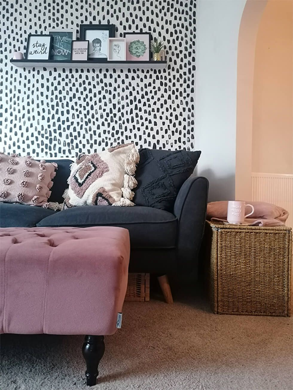 Grey sofa and pink ottoman in a living room with polka dot walls