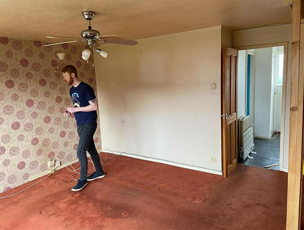 empty living room with red carpet floors and wallpaper