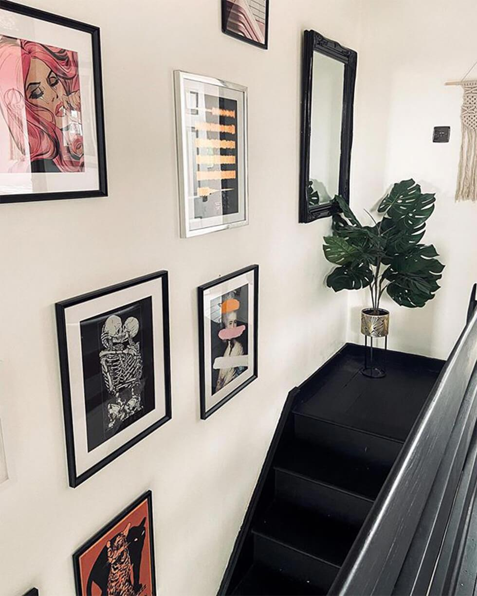 gallery wall landing by black wooden staircase