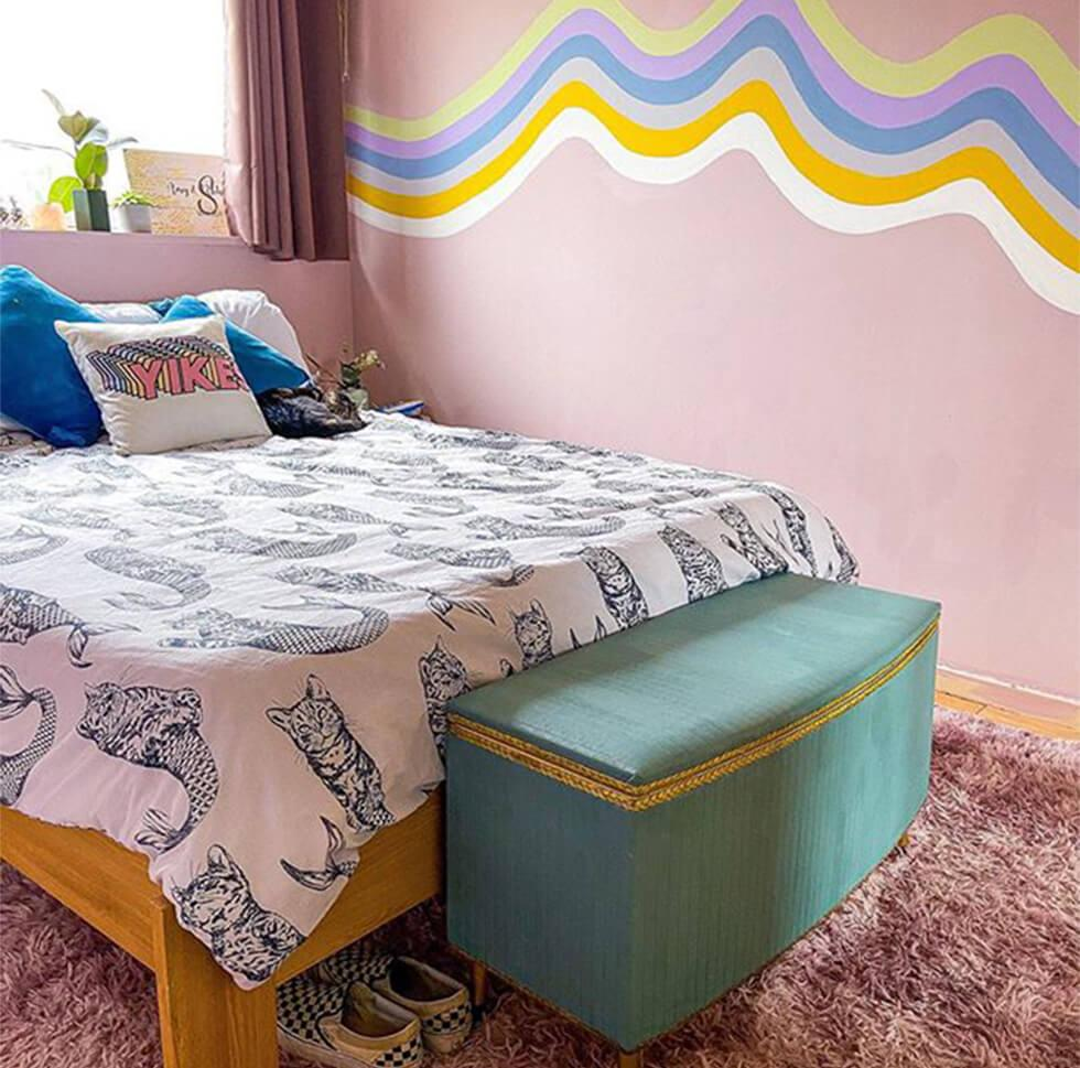wave mural in a pink bedroom with a shaggy pink rug and teal ottoman