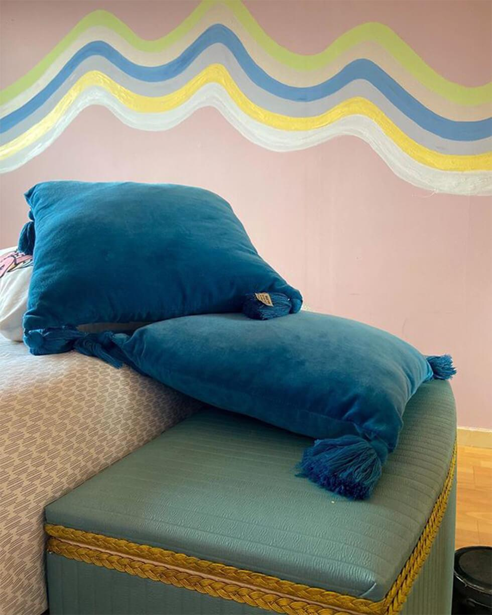 blue pillows in a pink bedroom with a wall mural