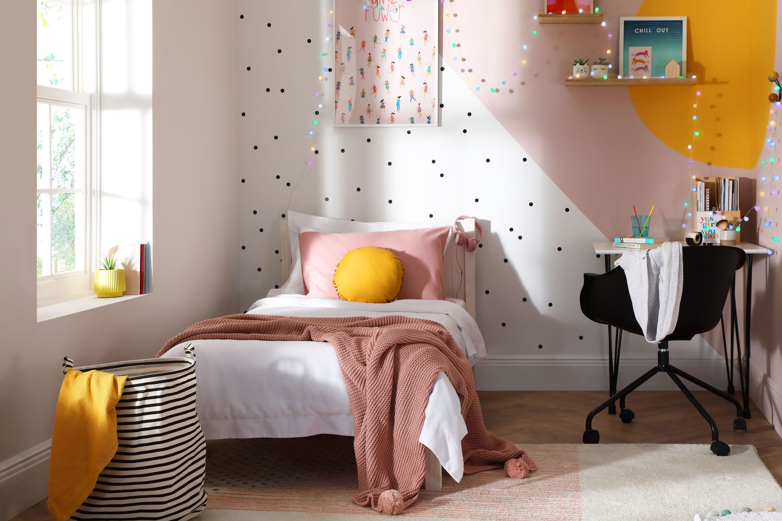 Bold yellow and pink feature wall with polka dots in a modern kids bedroom