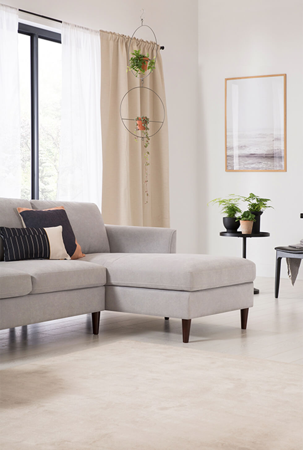 Grey plush fabric corner sofa in a modern white living room with indoor plants