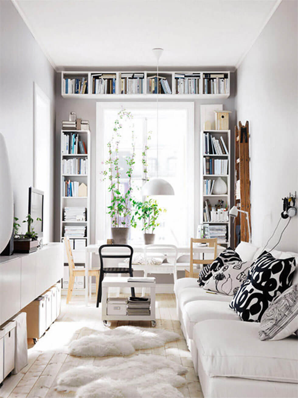 Small white living room with a white sofa, rug and bookshelves