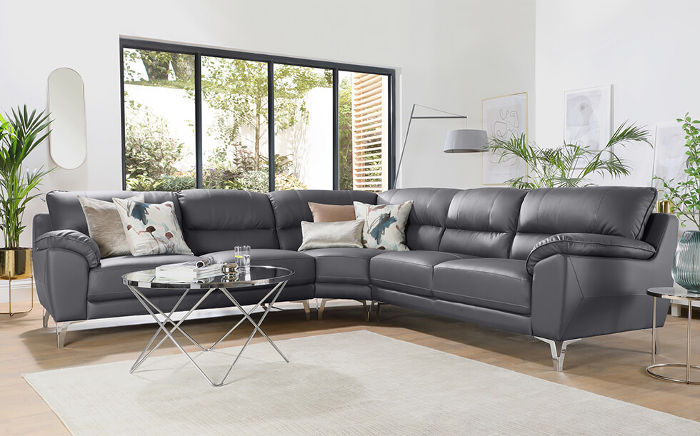 grey leather corner sofa with chrome detailing in a modern white living room