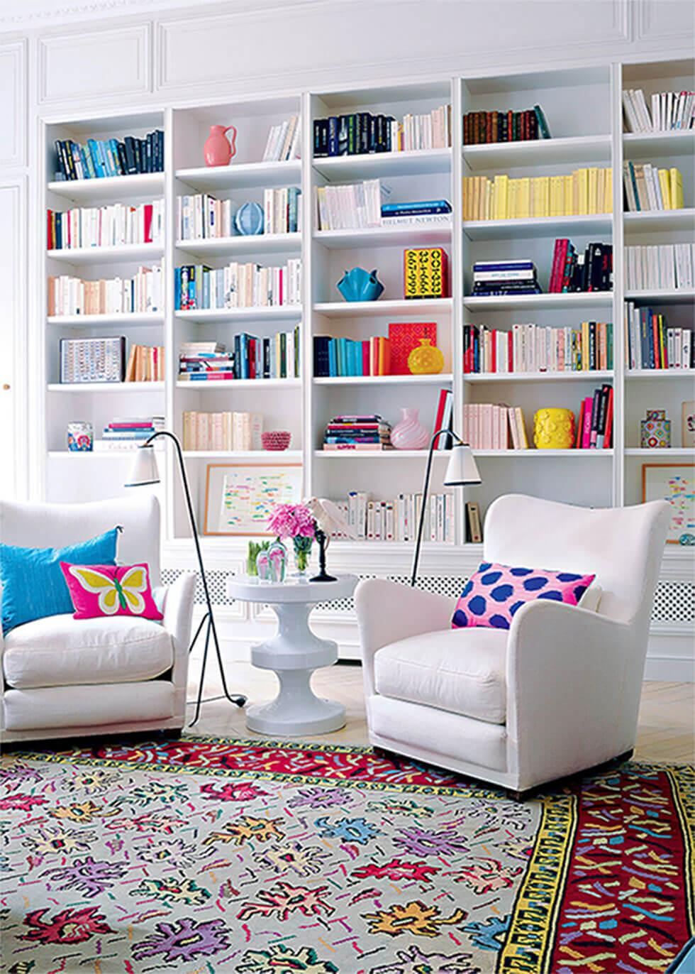 Living room with white armchairs and bookshelves, with colourful rug, cushion and decor.