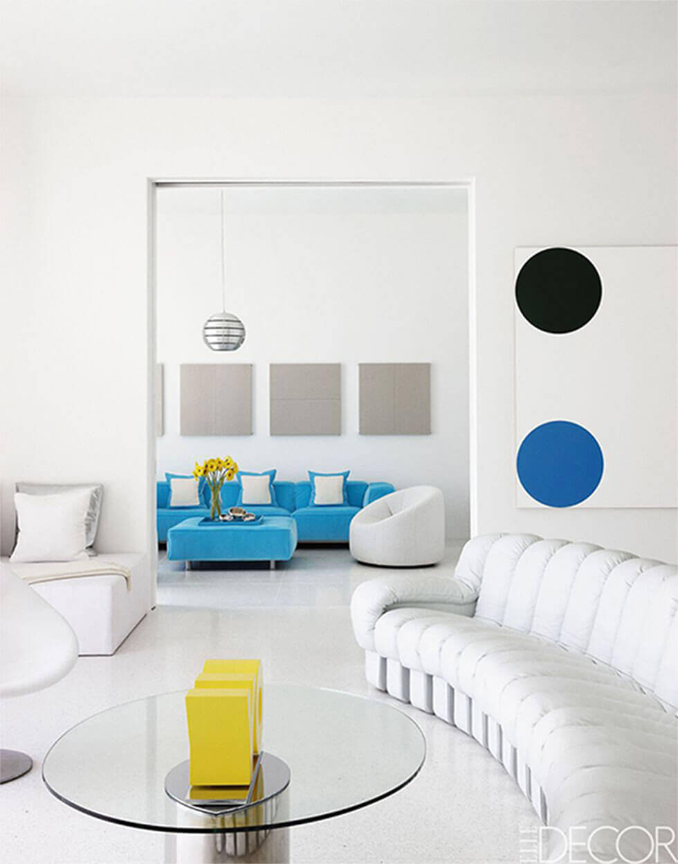 An all-white living room with vibrant pops of yellow and blue.