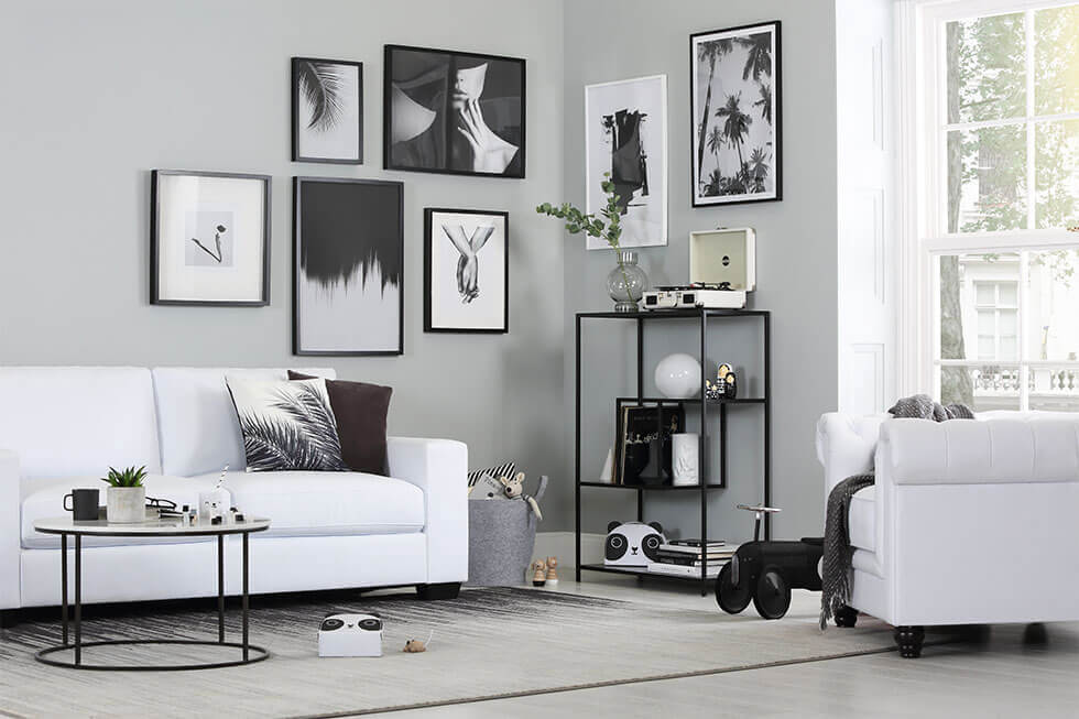 Modern white living room with white leather sofa set and black table and decor.