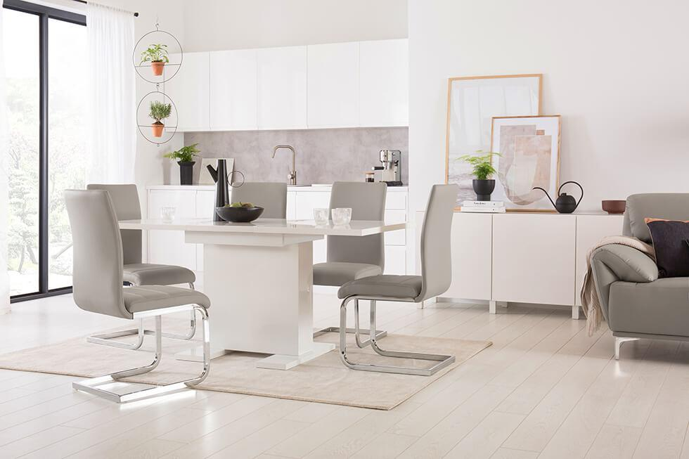Clean, bright open plan kitchen, dining and living room with white high gloss table and taupe dining chairs and sofa.