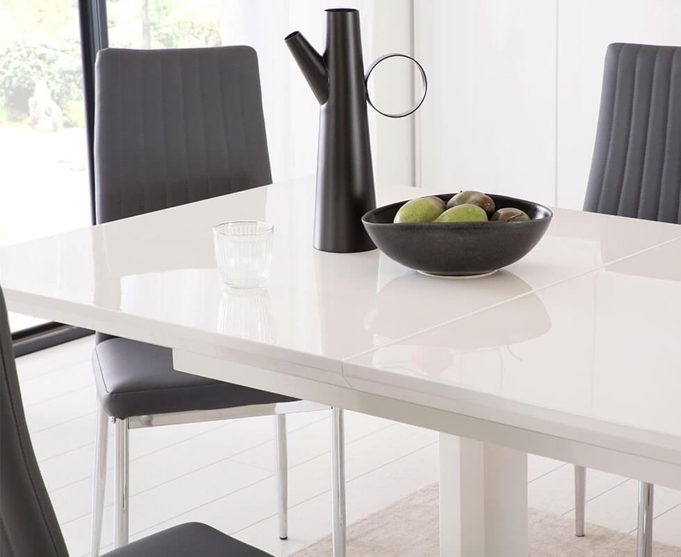 High gloss white table with black leather chairs with chrome legs in a simple, neutral dining room.