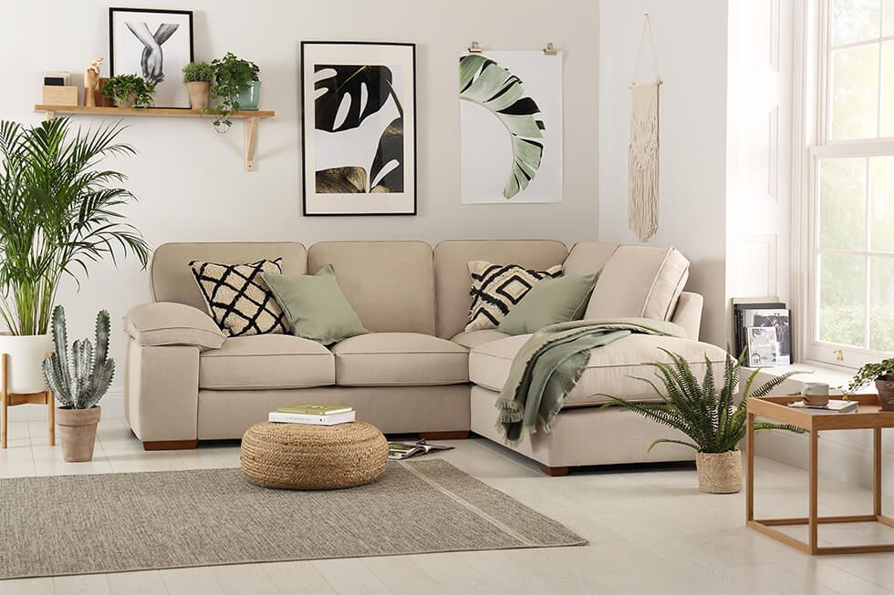 A relaxing living room with a beige linen corner sofa, green cushions, plants and natural artwork