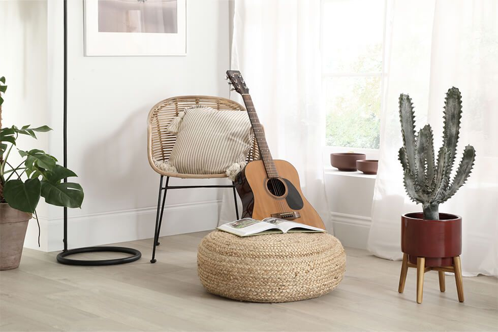 A chill out corner with a rattan armchair, guitar and potted plants