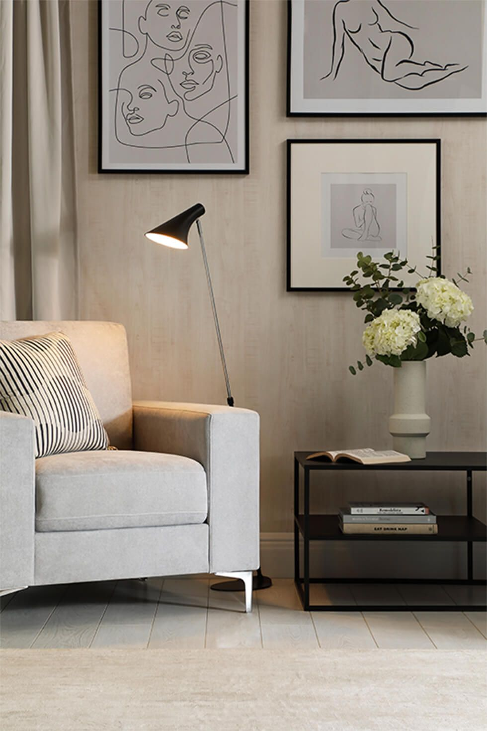 A chill out corner in a modern living room with a grey armchair against a gallery wall