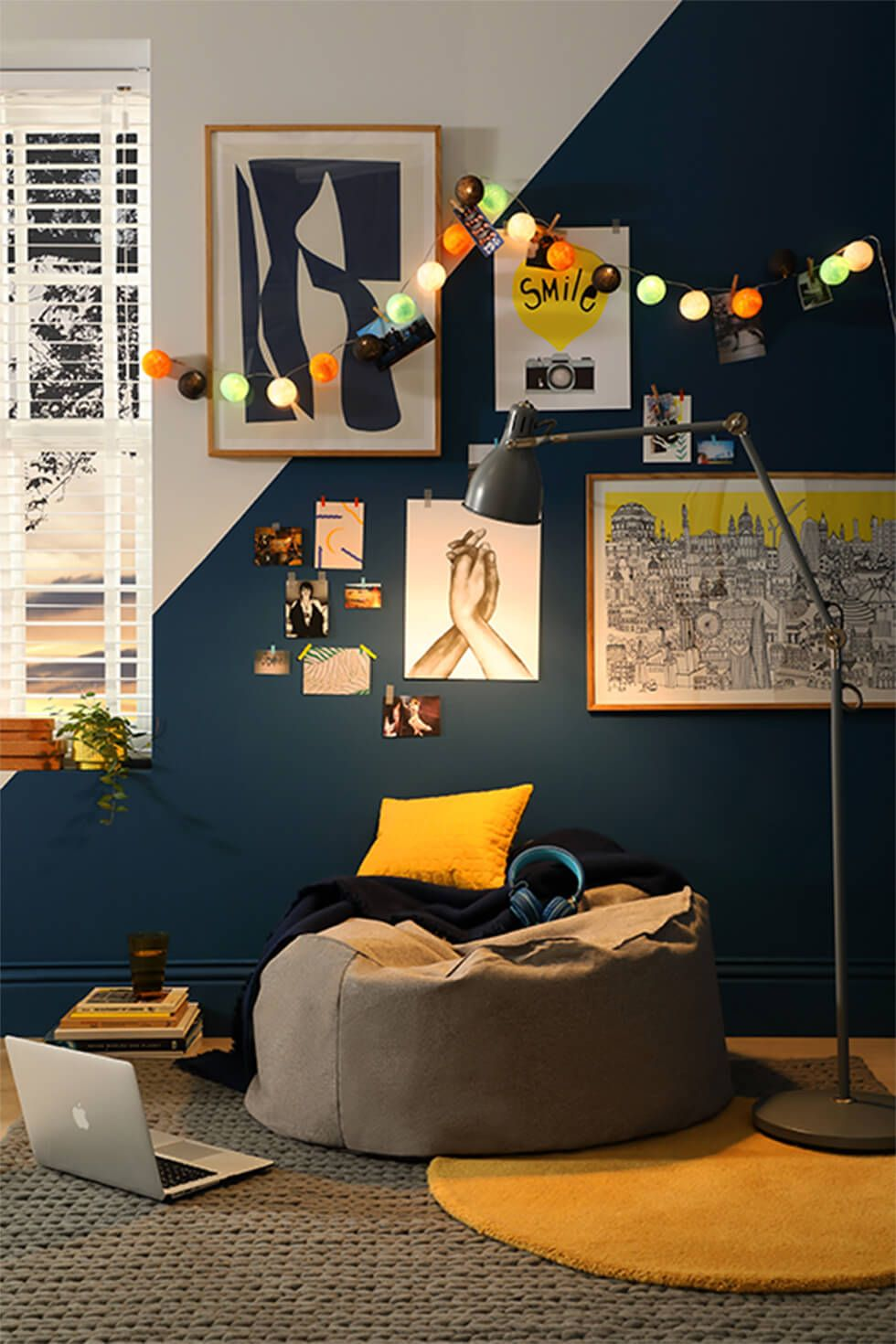 A relaxation corner in a teenager's room with a geometric wall, bean bag and string lights