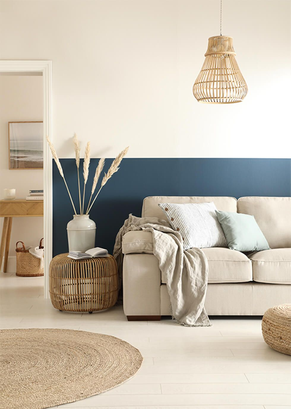 A calming living room with a half painted blue wall and linen sofa