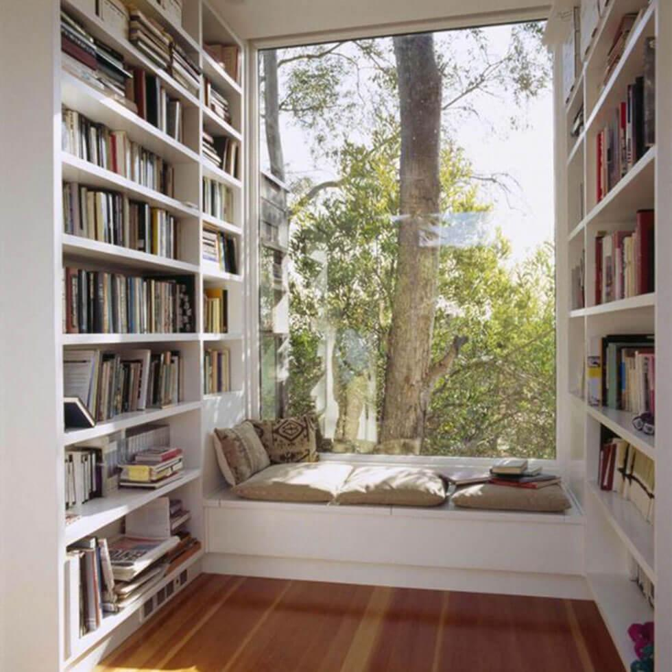 simple white bookcase and reading nook with nature views