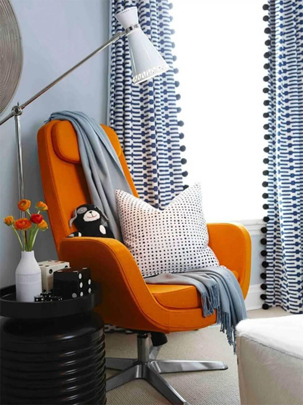 cosy blue reading nook with orange armchair in kids bedroom