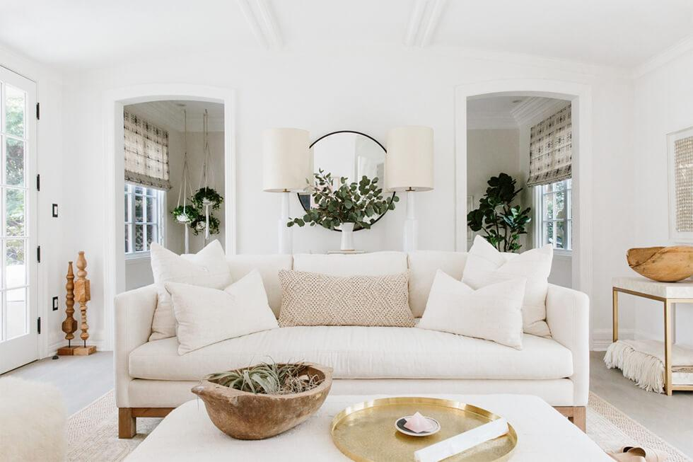 All white living room with large sofa and natural elements