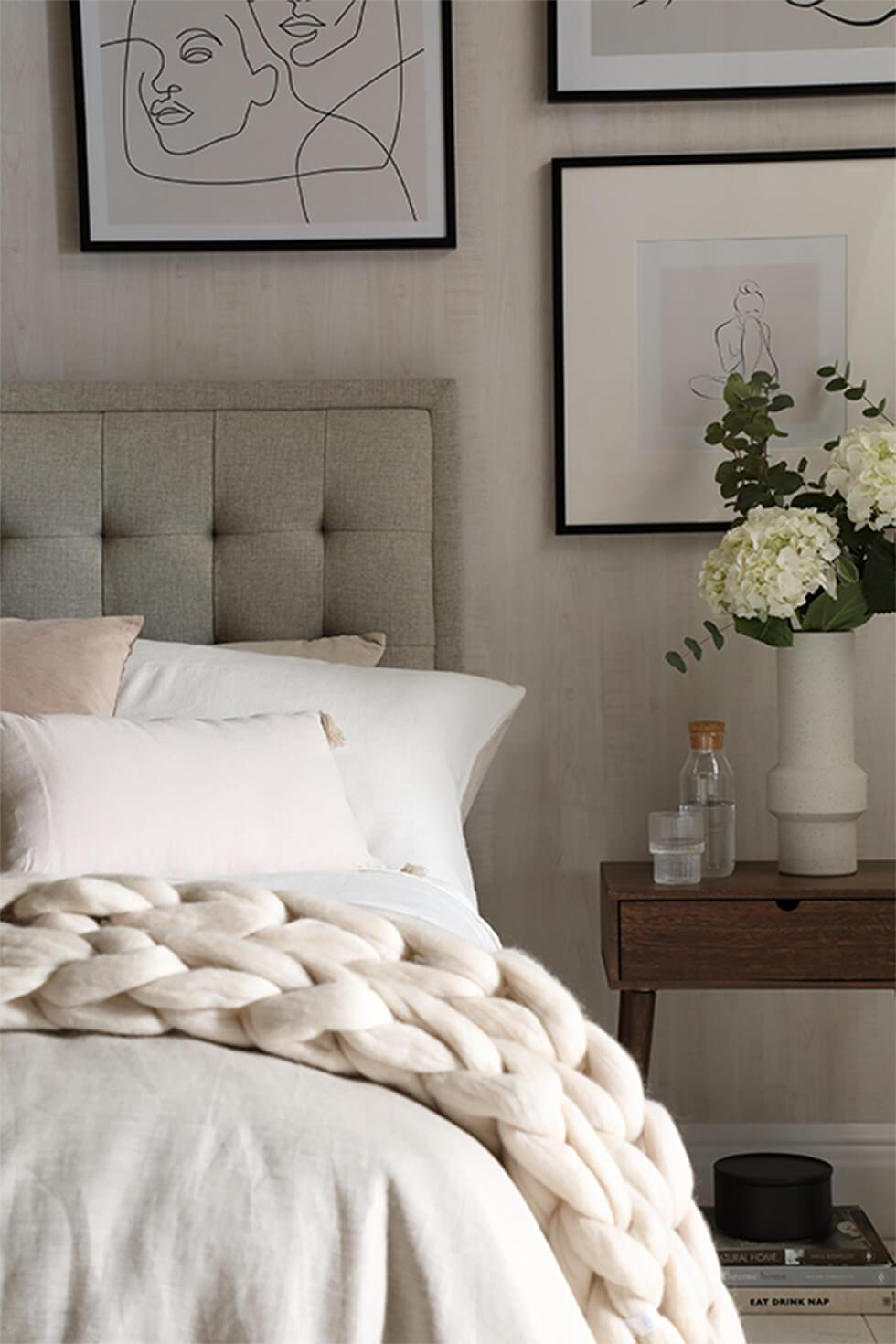 Neutral bedroom with white bedspread and throw with tufted headboard