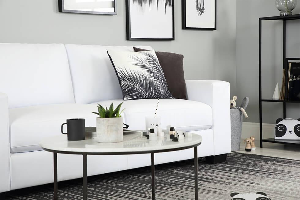 Bright white living room with white leather sofa and black decor
