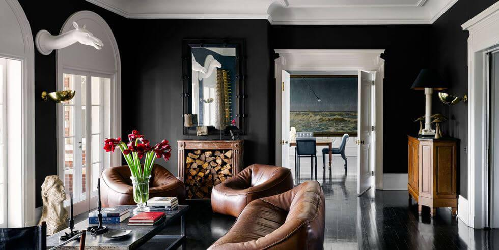 Black living room with brown leather chairs, wooden furniture and white ceiling