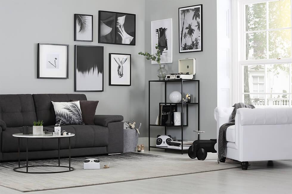 Monochrome living room with black sofa, white armchair and artwork