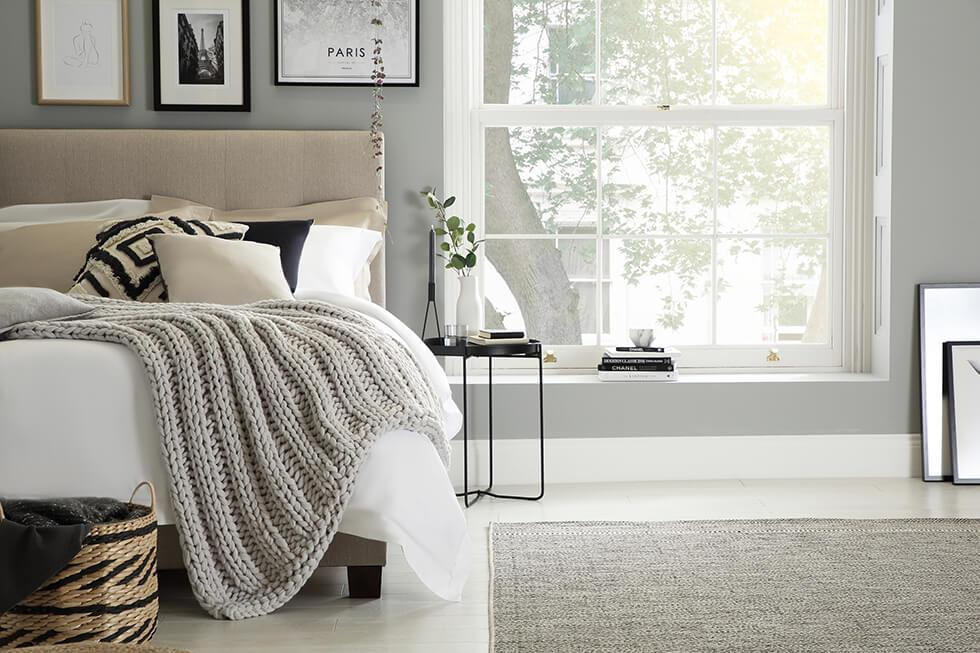 Cosy neutral bedroom with grey walls
