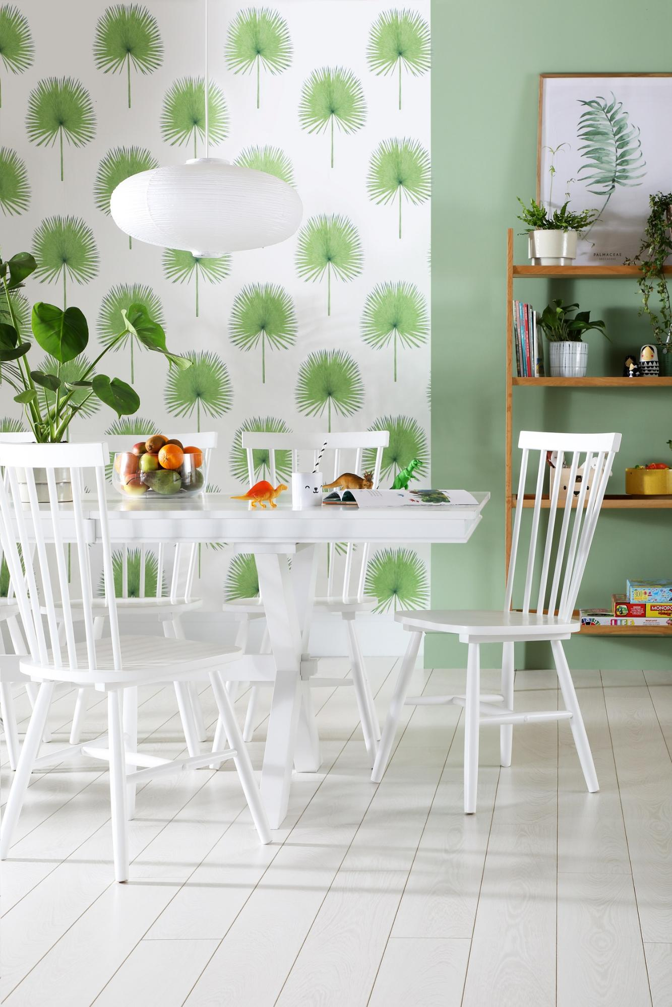 Tropical dining room with sage walls, palm print wallpaper and white dining set