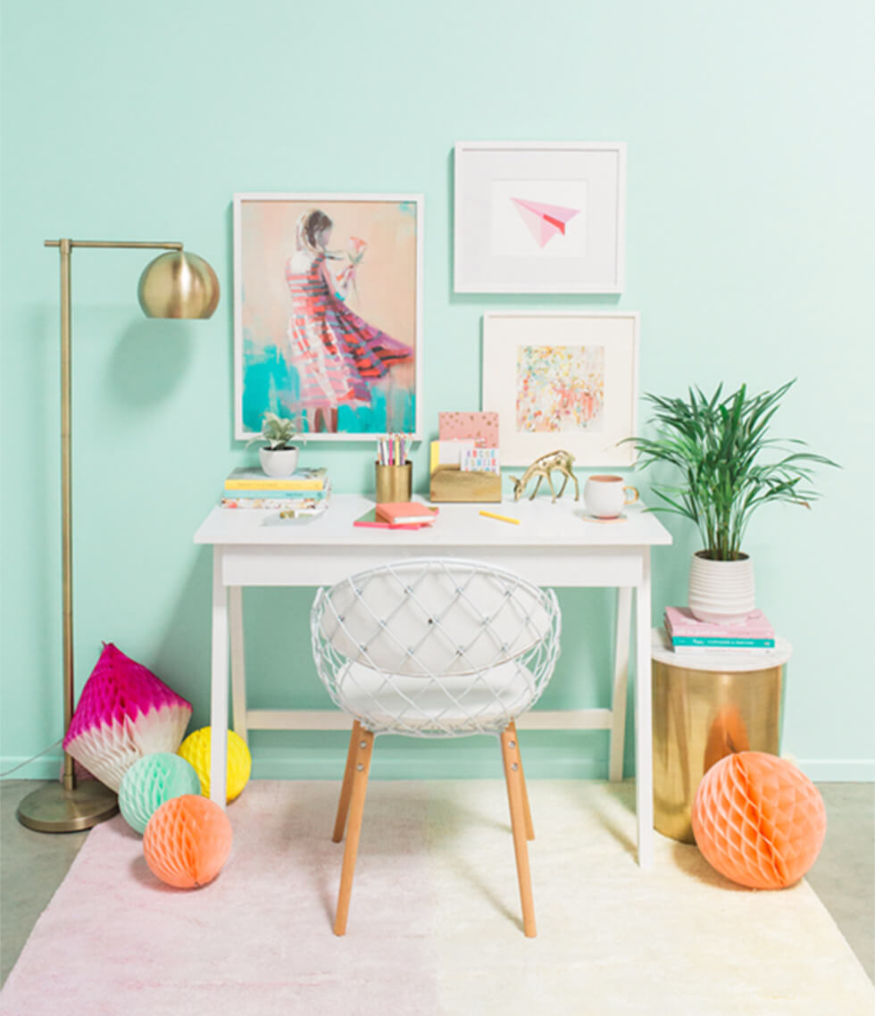 Home office with turquoise walls and brass accessories