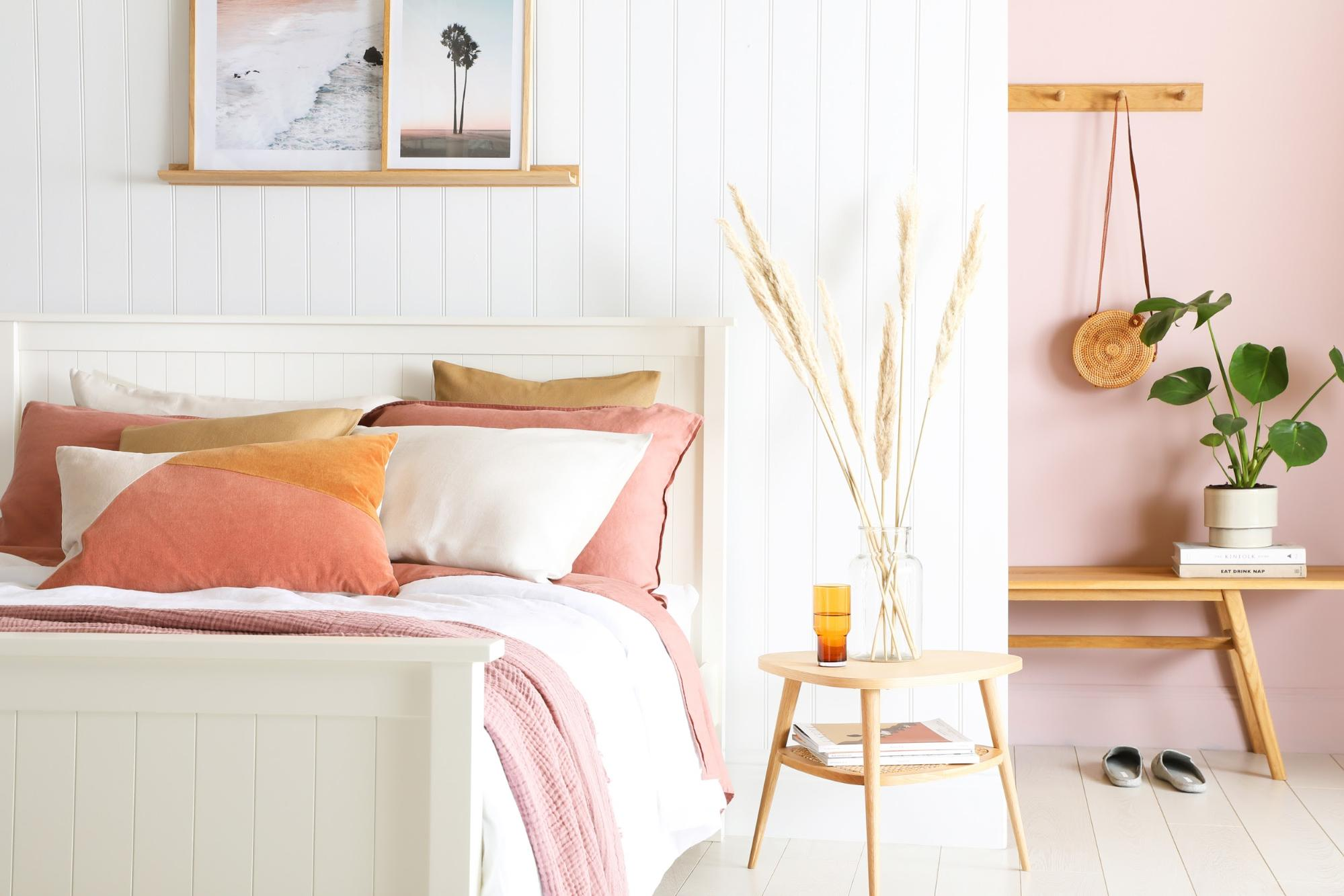 Bedroom with white wall panels and pink touches