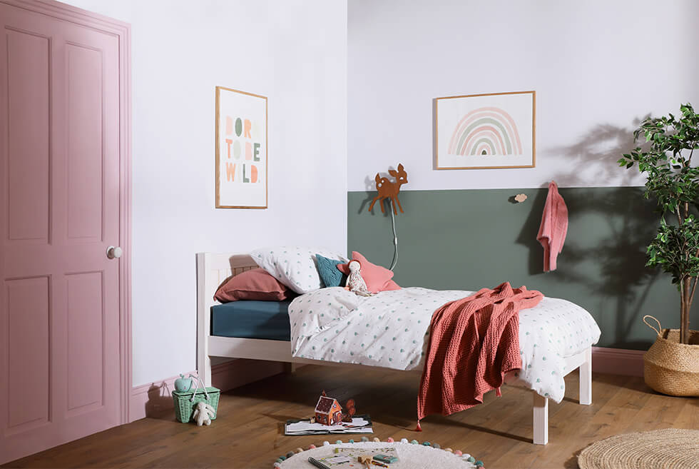 Children's bedroom with a white and green half-painted wall and pink door