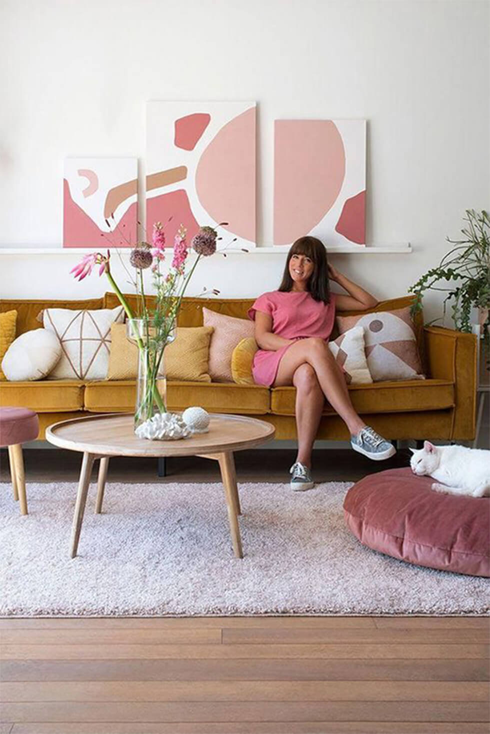 Girl sitting on mustard yellow sofa with pink accessories in stylish living room