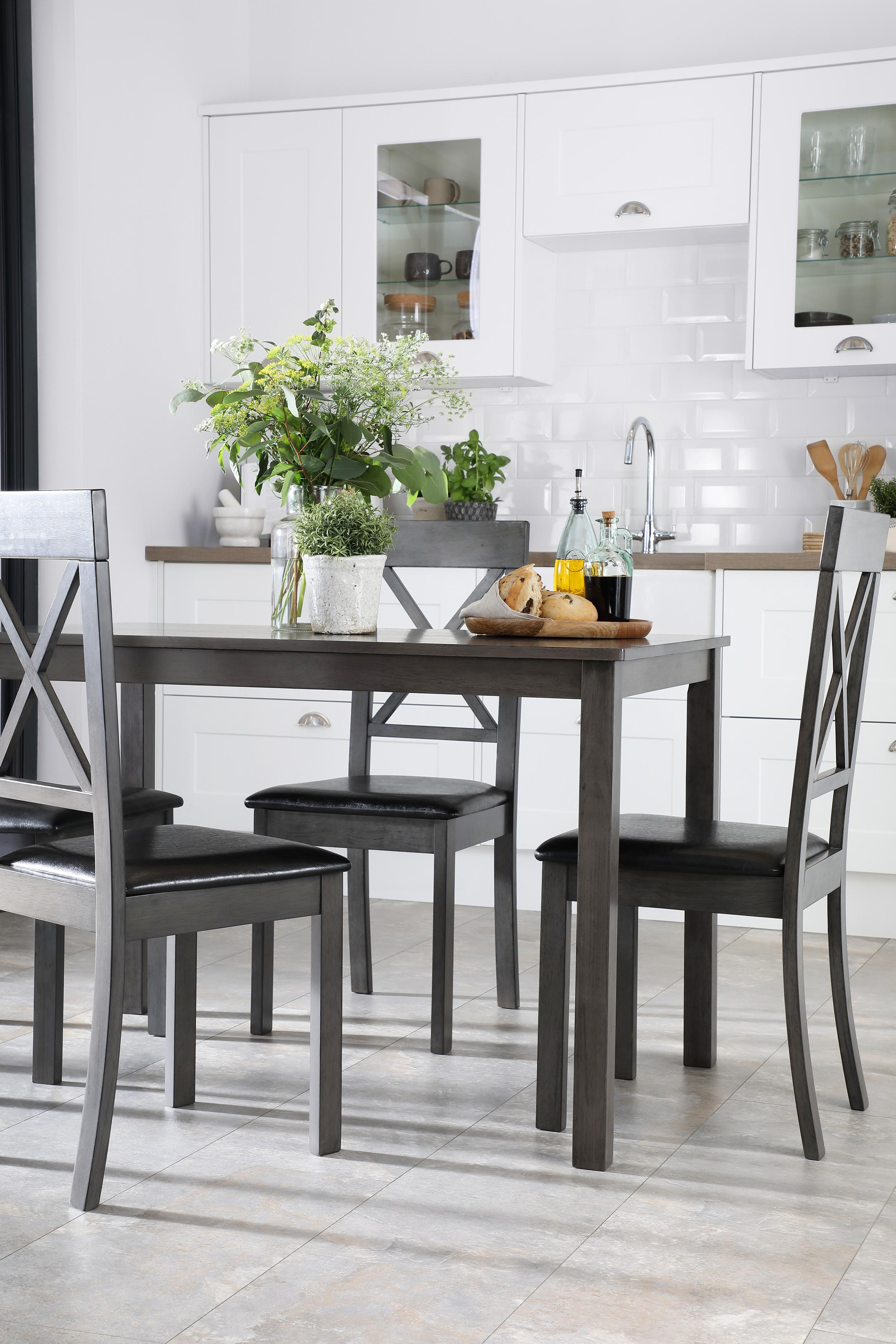 painted black wooden dining table with x back d ining chairs in a contemporary open plan space