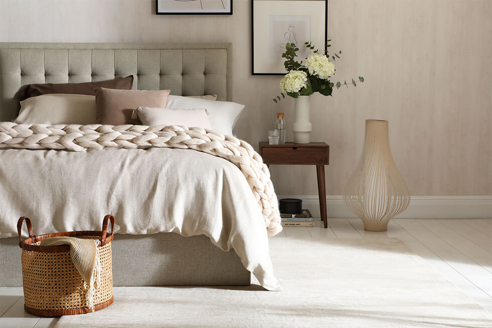 Neutral bedroom with fabric bed, knitted throw and flowers