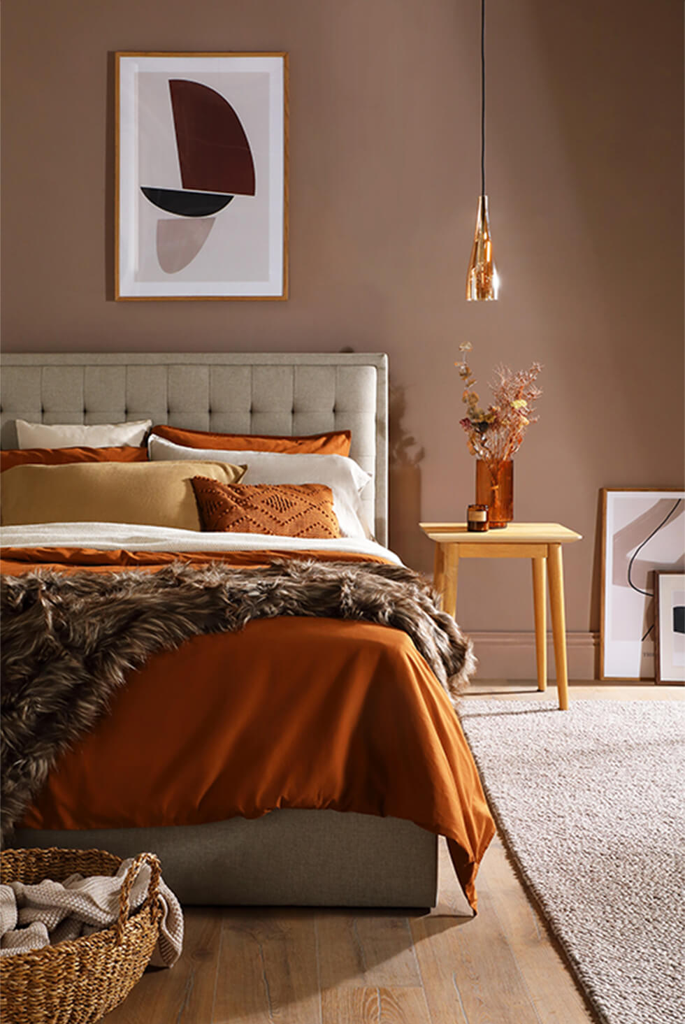 Dramatic neutral bedroom with a fabric bed, and brown and gold accents