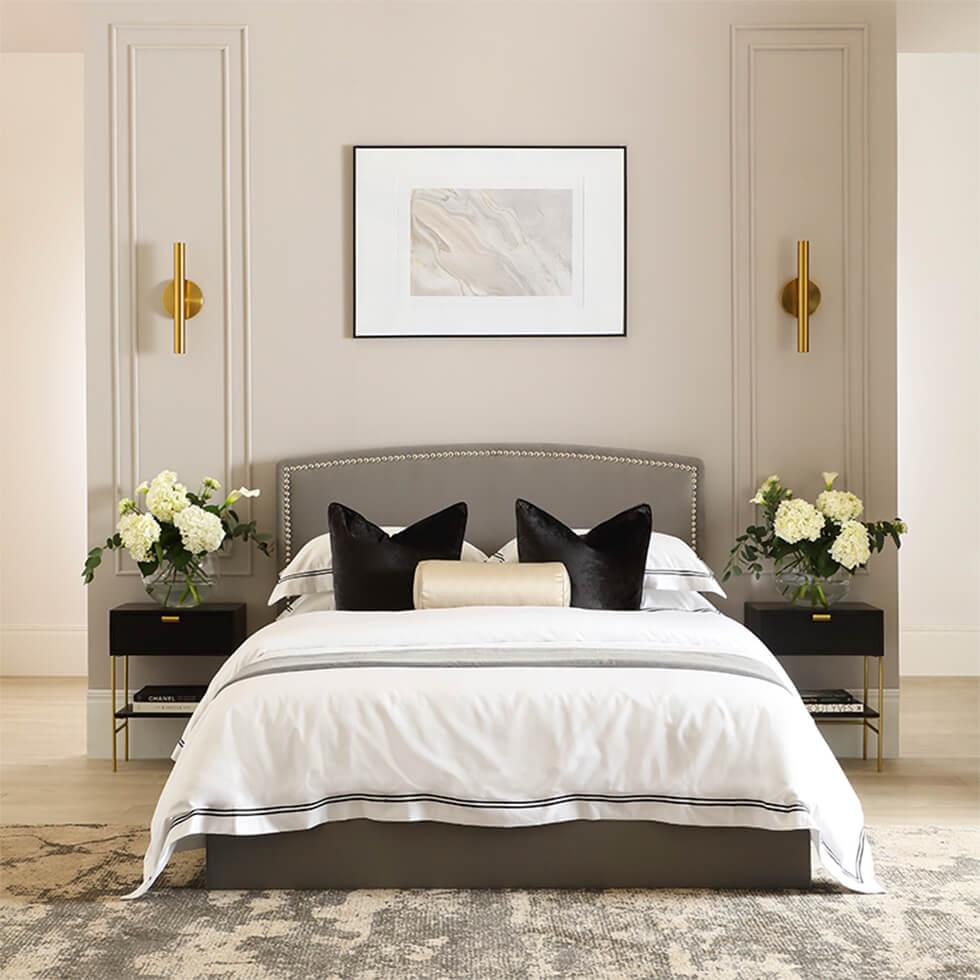 Neutral bedroom with grey fabric bed, framed art and fresh flowers